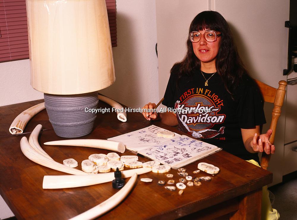 Inupiat pilot Ellen Paneok scrimshawing walrus ivory at her home in Barrow, Alaska.