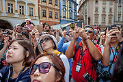 "Tourist groups and visitors watching and documenting the Prague ""Orloj"" performance at Old Town Square in Prague. One of the main attractions on the square is The Prague astronomical clock, or Prague orloj (Czech: Pražský orloj) which is a medieval astronomical clock. The clock was first installed in 1410, making it the third-oldest astronomical clock in the world and the oldest one still operating."