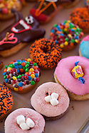 """Voodoo Doughnut, Too! located in NE Portland, Oregon features unusual doughnuts and is owned by Tres Shannon and Kenneth """"Cat Daddy"""" Pogson.  A field of doughnuts: The Loop (fruit loops on top), Captain My Captain (captain crunch topping), Marshall Mathers (m&m topping, aka EMINEM), Grape Ape (purple), Miami Viceberry (hot pink with blue),  Double Bubble (with gum on top), Neopolitan (chocolate cake doughnut with pink strawberry dust and marshmallows), plain cake with orange and brown sprinkles"""