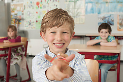 Schoolboy with a slingshot and smiling in classroom, Munich, Bavaria, Germany