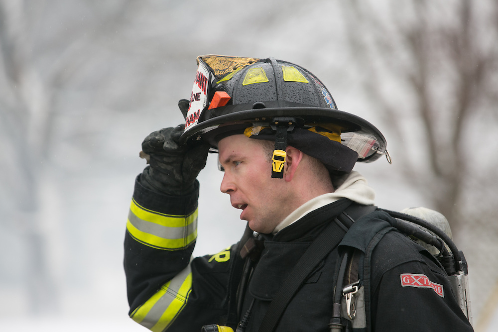 Hingham, MA 02/11/2013.A Hingham firefighter cools off at the scene of a 3 alarm house fire at 276 East St. in Hingham on Monday, February 11..Alex Jones / www.alexjonesphoto.com