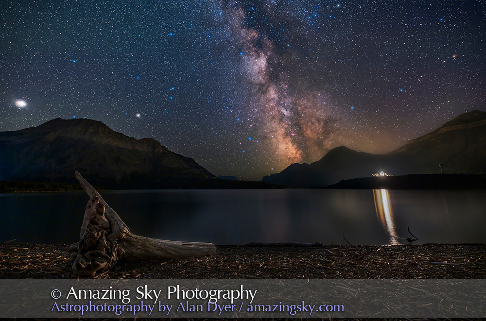 The northern summer Milky Way over Middle Waterton Lake at Driftwood Beach in Waterton Lakes National Park, Alberta on a July night. Sagittarius is at centre, with the pink Lagoon Nebula, M8, right of centre. The Dark Horse complex of dust lanes is over the peak at right. The Scutum Starcloud is at top centre. The bright object at far left is Jupiter, with dimmer Saturn to the right, with both over Vimy Peak and in Capricornus or thereabouts!<br /> <br /> This is a blend of tracked exposures for the sky and untracked exposures for the ground: a stack of 4 x 2-minute tracked at f/2.8 and ISO 1600 for the sky, blended with a single 8-minute untracked at f/5.6 and ISO 800 for the ground, taken with Long Exposure Noise Reduction on to eliminate most thermal hot pixels this warm night. A tracked 2-minute exposure through an Kase/Alyn Wallace Starglow filter adds the star glow effect. An additional short 30-second exposure at ISO 400 and f/4 is for the lights of the Prince of Wales Hotel and their reflections, to preevent them from overexposing too much which they would in the long ground exposure. <br /> <br /> Forest fire smoke moving in added some haze and lowered contrast.<br /> <br /> The sky tracker was the Star Adventurer Mini which worked perfectly. The camera was the Canon ESO Ra and lens the Canon 15-35mm RF at 15mm.