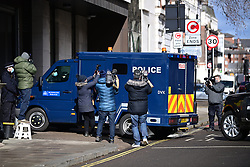 © Licensed to London News Pictures. 13/03/2021. London, UK.  Police officers escort a police vehicle carrying a prisoner in to Westminster Magistrates Court where murder suspect Wayne Couzens is due to appear. Couzens, A serving Met Police officer, has been charged with with the kidnap and murder of Sarah Everard, who disappeared as she walked home in Clapham, south London. The body of Sarah Everard was later discovered woodland in Kent more than a week after she was last spotted on 3 March. Photo credit: Ben Cawthra/LNP
