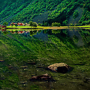 I have seen this beautiful reflection on my way to the west of Norway. I can tell you that every meter you will be amazed by the natural landscapes in this region. Unfortunately I didn't have time to stop and take pictures so I took this one in the car. My colleague was the driver ;). The picture has been cropped for the road lines.   Please feel free to check my photos here or find me by: |Website |,|Facebook page|, |Instagram |,Google+ |.Twitter |.