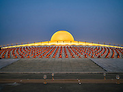 """22 FEBRUARY 2016 - KHLONG LUANG, PATHUM THANI, THAILAND: Buddhist monks sit around the chedi during Makha Bucha Day at Wat Phra Dhammakaya.  Makha Bucha Day is a public holiday in Cambodia, Laos, Myanmar and Thailand. Many people go to the temple to perform merit-making activities on Makha Bucha Day, which marks four important events in Buddhism: 1,250 disciples came to see the Buddha without being summoned, all of them were Arhantas, Enlightened Ones, and all were ordained by the Buddha himself. The Buddha gave those Arhantas the principles of Buddhism, called """"The ovadhapatimokha"""". Those principles are:  1) To cease from all evil, 2) To do what is good, 3) To cleanse one's mind. The Buddha delivered an important sermon on that day which laid down the principles of the Buddhist teachings. In Thailand, this teaching has been dubbed the """"Heart of Buddhism."""" Wat Phra Dhammakaya is the center of the Dhammakaya Movement, a Buddhist sect founded in the 1970s and led by Phra Dhammachayo. The temple is famous for the design of its chedi, which some have likened to a flying saucer or UFO.           PHOTO BY JACK KURTZ"""