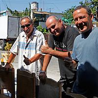 Central America, Cuba, Havana. Men of Muralenado Community Project enjoying live music.