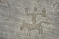 Petroglyph, rock carving, of a man on a horse. Carved by the ancient Camunni people in the iron age between 900-1200 BC. Rock no 6, Foppi di Nadro, Riserva Naturale Incisioni Rupestri di Ceto, Cimbergo e Paspardo, Capo di Ponti, Valcamonica (Val Camonica), Lombardy plain, Italy .<br /> <br /> Visit our PREHISTORY PHOTO COLLECTIONS for more   photos  to download or buy as prints https://funkystock.photoshelter.com/gallery-collection/Prehistoric-Neolithic-Sites-Art-Artefacts-Pictures-Photos/C0000tfxw63zrUT4<br /> If you prefer to buy from our ALAMY PHOTO LIBRARY  Collection visit : https://www.alamy.com/portfolio/paul-williams-funkystock/valcamonica-rock-art.html