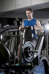 Mid adult man doing exercise on machine in the gym, Bavaria, Germany