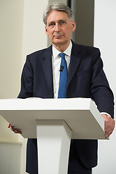 "© Licensed to London News Pictures. 03/05/2017. London, UK.  Chancellor of the Exchequer PHILLIP HAMMOND speaks at a General Election Campaign event featuring a poster of Labour party leader JEREMY CORBYN with the slogan ""More debt, higher tax."" Photo credit: Ray Tang/LNP"