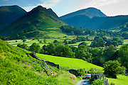Motoring holiday tourists driving through Cumbrian mountain range near Derwentwater in Lake District National Park, UK