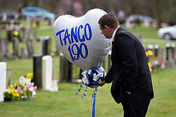 """© licensed to London News Pictures. Stafford, UK  17/03/2012. A mourner holds on to a balloon reading """"Tango 190"""", PC Rathband's call sign, after the funeral of PC David Rathband. Photo credit should read Joel Goodman/LNP"""