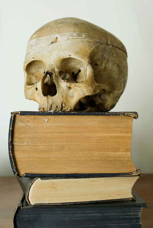 A human skull resting on a stack of old medical textbooks. England 2007.