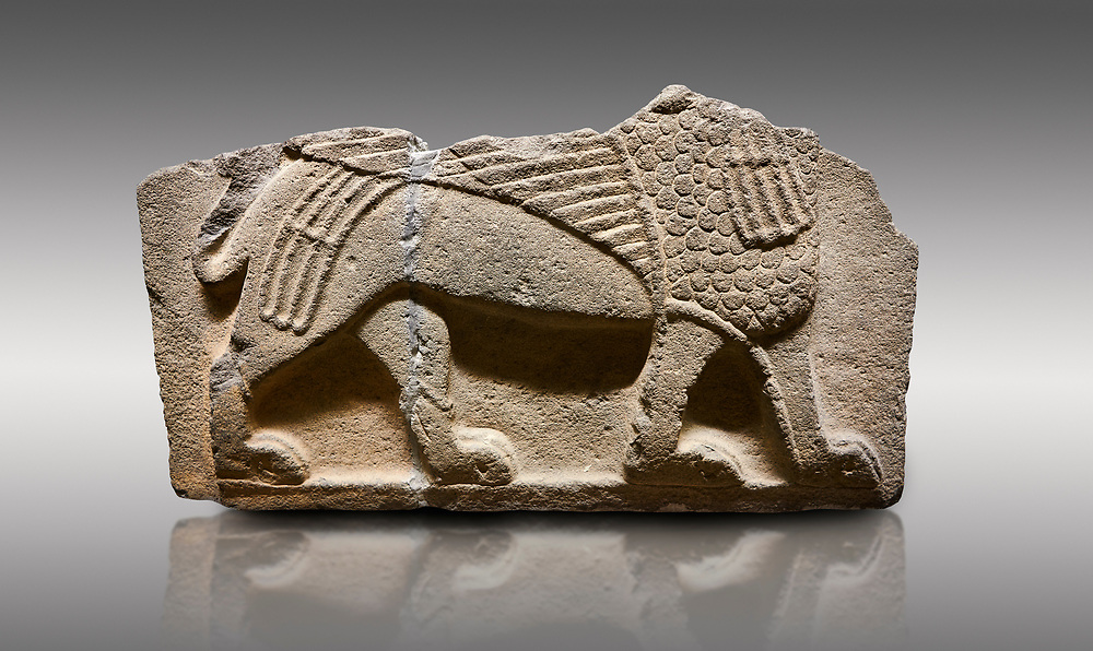 Picture & image of Hittite monumental relief sculpted orthostat stone panel from Water Gate Basalt, Karkamıs, (Kargamıs), Carchemish (Karkemish), 900-700 B.C. Anatolian Civilisations Museum, Ankara, Turkey.<br /> <br />  A portion of the body and the feet of the Sphinx. Its chest was processed as fish flakes. Parallel lines on its wings draw attention.  <br /> <br /> On a gray background. .<br />  <br /> If you prefer to buy from our ALAMY STOCK LIBRARY page at https://www.alamy.com/portfolio/paul-williams-funkystock/hittite-art-antiquities.html  - Type  Karkamıs in LOWER SEARCH WITHIN GALLERY box. Refine search by adding background colour, place, museum etc.<br /> <br /> Visit our HITTITE PHOTO COLLECTIONS for more photos to download or buy as wall art prints https://funkystock.photoshelter.com/gallery-collection/The-Hittites-Art-Artefacts-Antiquities-Historic-Sites-Pictures-Images-of/C0000NUBSMhSc3Oo