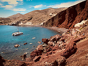 High angle view of Red Beach, which is a volcanic sand beach on the Aegean island of Santorini with catamaran