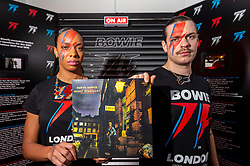 © Licensed to London News Pictures. 25/10/2021. LONDON, UK.  Store staff with the Ziggy Stardust album at the opening of a David Bowie pop-up shop in Heddon Street in the West End.  Open 75 days before the late singer's 75th birthday, the pop-up is located close to where Bowie posed as Ziggy Stardust on the cover of his 1972 album The Rise and Fall of Ziggy Stardust and the Spider from Mars.  The store sells limited edition records and memorabilia curated by his estate and will be open until January 2022. A sister shop will open in New York and both form part of a year long celebration of David Bowie's 75th birthday.  Photo credit: Stephen Chung/LNP