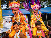 "05 APRIL 2015 - CHIANG MAI, CHIANG MAI, THAILAND:  Tai Yai boys being ordained as Buddhist novices parade around Wat Pa Pao in Chiang Mai with their families during the second day of the three day long Poi Song Long Festival in Chiang Mai. The Poi Sang Long Festival (also called Poy Sang Long) is an ordination ceremony for Tai (also and commonly called Shan, though they prefer Tai) boys in the Shan State of Myanmar (Burma) and in Shan communities in western Thailand. Most Tai boys go into the monastery as novice monks at some point between the ages of seven and fourteen. This year seven boys were ordained at the Poi Sang Long ceremony at Wat Pa Pao in Chiang Mai. Poy Song Long is Tai (Shan) for ""Festival of the Jewel (or Crystal) Sons.   PHOTO BY JACK KURTZ"