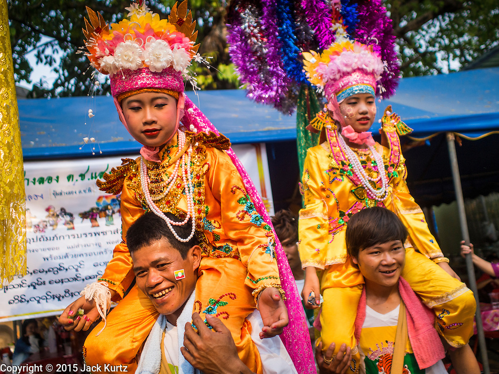 """05 APRIL 2015 - CHIANG MAI, CHIANG MAI, THAILAND:  Tai Yai boys being ordained as Buddhist novices parade around Wat Pa Pao in Chiang Mai with their families during the second day of the three day long Poi Song Long Festival in Chiang Mai. The Poi Sang Long Festival (also called Poy Sang Long) is an ordination ceremony for Tai (also and commonly called Shan, though they prefer Tai) boys in the Shan State of Myanmar (Burma) and in Shan communities in western Thailand. Most Tai boys go into the monastery as novice monks at some point between the ages of seven and fourteen. This year seven boys were ordained at the Poi Sang Long ceremony at Wat Pa Pao in Chiang Mai. Poy Song Long is Tai (Shan) for """"Festival of the Jewel (or Crystal) Sons.   PHOTO BY JACK KURTZ"""
