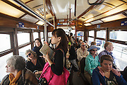 Passengers in 28 tram in Lisbon grabbing their hands while travelling standing.
