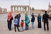 Egyptian tourists buy snacks from a local man in front of the ancient Egyptian columns of Luxor Temple, Luxor, Nile Valley, Egypt. But stallholders await more visitors during the tourist downturn. According to the country's Ministry of Tourism, European visitors to Egypt is down by up to 80% in 2016 from the suspension of flights after the downing of the Russian airliner in Oct 2015. Euro-tourism accounts for 27% of the total flow and in total, tourism accounts for 11.3% of Egypt's GDP. The temple was built by Amenhotep III, completed by Tutankhamun then added to by Rameses II. Towards the rear is a granite shrine dedicated to Alexander the Great and in another part, was a Roman encampment. The temple has been in almost continuous use as a place of worship right up to the present day.