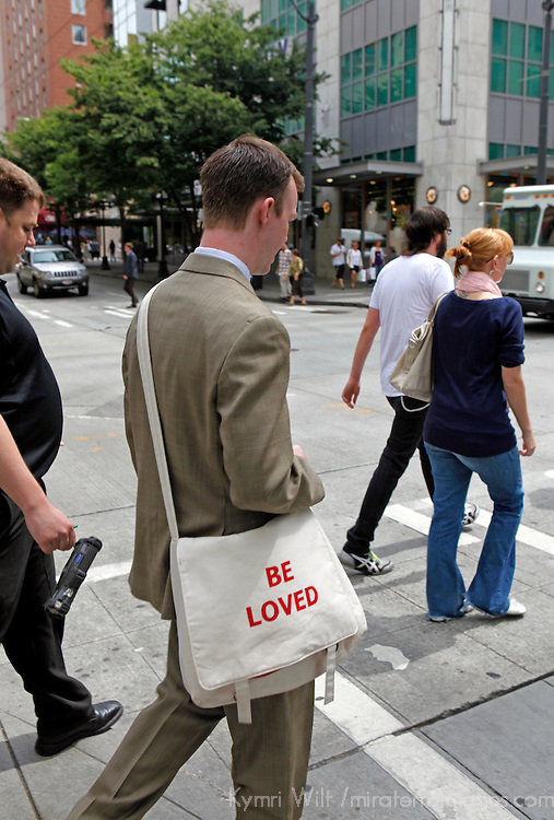 """North America, USA, Washington, Seattle. Pedestrian with tote """"be loved""""."""