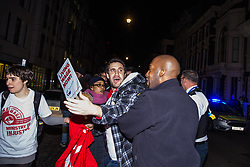 London, UK. 12th February, 2019. A police officer pushes Petros Elia, General Secretary of grassroots trade union United Voices of the World, out of the road during a protest outside the Gadson Club in Pall Mall on the occasion of a reception with Justice Secretary David Gauke against his refusal to negotiate with the trade union over their demands for the London Living Wage, annual leave and sick pay for outsourced cleaners, security guards and receptionists working at the Ministry of Justice, all of whom have been on strike for varying periods recently. The Gadson Club is the official alumni club for the Oxford University Conservative Association.