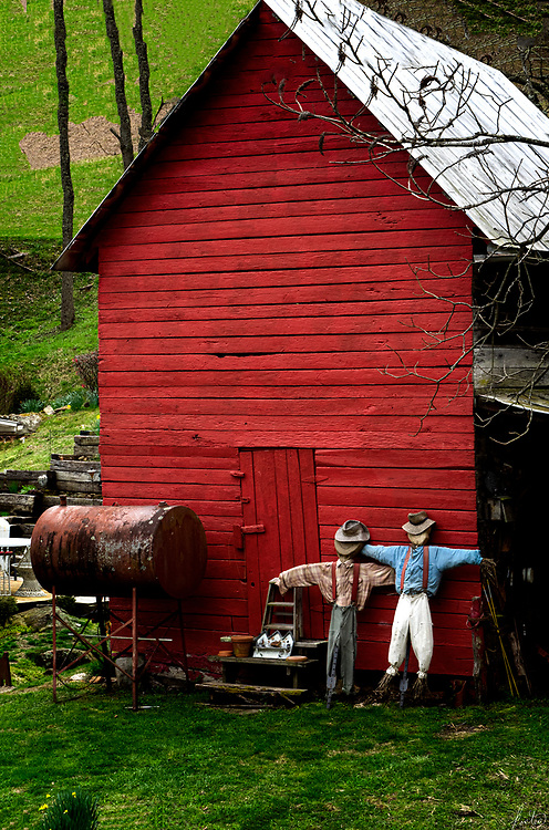 Two scarecrows leaning up againt a red barn near Burnsville, North Carolina