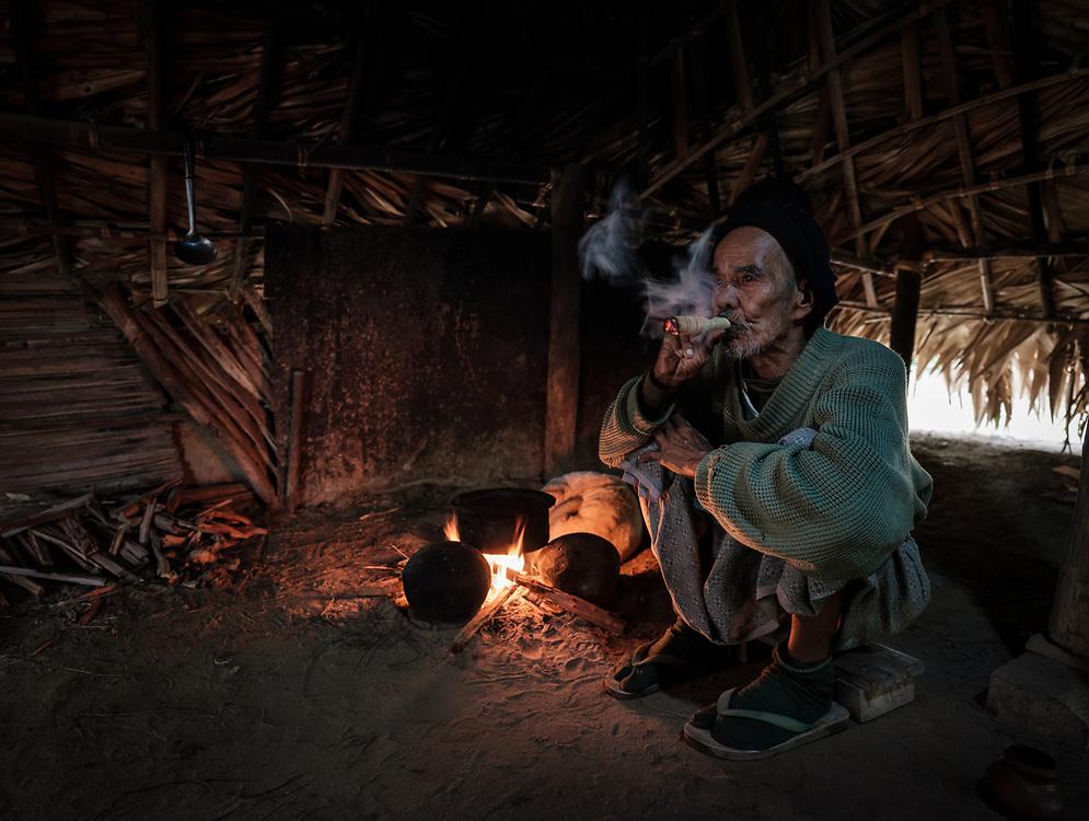 BAGAN, MYANMAR - CIRCA DECEMBER 2017: Old man from a village around Bagan smoking a cigar in his kitchen.