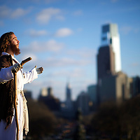 """With the Philadelphia skyline behind him, Michael Grant, 28, """"Philly Jesus,"""" looks towards the afternoon sun.  Nearly everyday for the last 8 months, Grant has dressed as Jesus Christ, and walked the streets of Philadelphia to share the Christian gospel by example.  He quickly acquired the nickname of """"Philly Jesus,"""" which he has gone by ever since."""