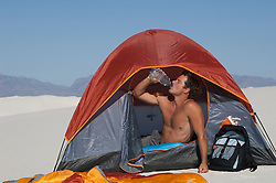 shirtless man drinking water while in a tent in White Sands, NM