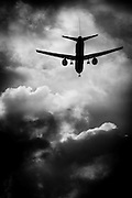 A silhouetted airplane flies into dark, ominous clouds. Missoula Photographer