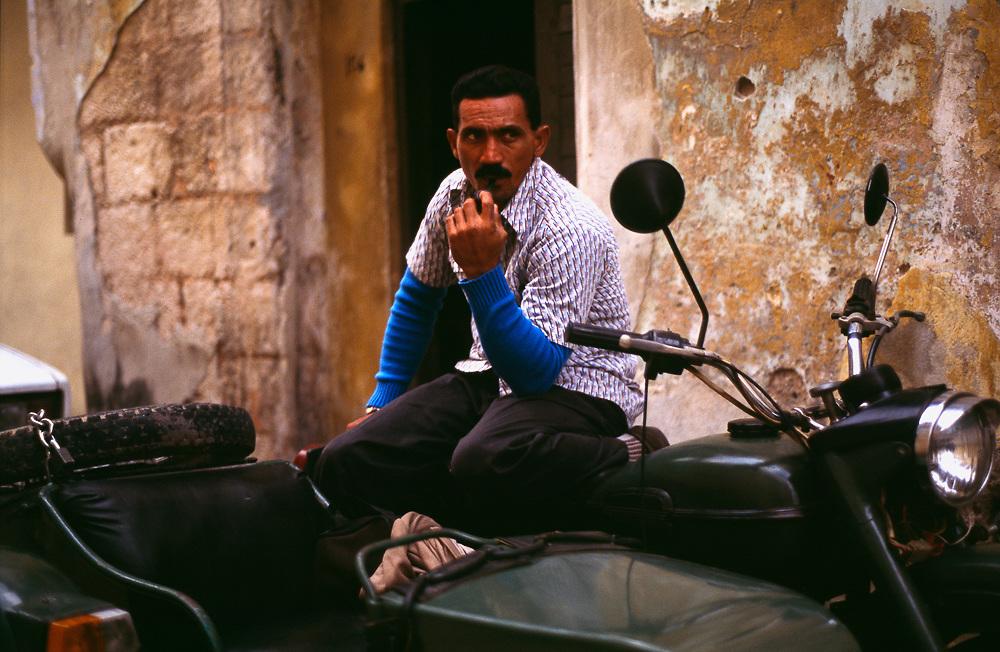 Portrait Cuban man kneeling on old motorbike with sidecar, Havana, Cuba.