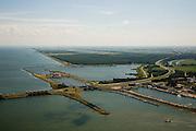 Nederland, Noord-Holland, Den Oever, 14-07-2008; waterkering tussen IJsselmeer en Waddenzee (onder in beeld); aanleg van de dijk vormde onderdeel Zuiderzeewerken, initiatief van ingenieur Cornelis Lely; in de dijk de Stevinsluizen, spuisluizen - uitwaterende sluizen; rechts boven de uitwateringssluizen de schutsluizen - schutsluis; op het tweede plan het Robbenoordbos in de Wieringermeer, met Radio en TV mast; de snelweg is rijksweg A7; . .luchtfoto (toeslag); aerial photo (additional fee required); .foto Siebe Swart / photo Siebe Swart