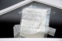 ©London News pictures. 09/03/11. A legal notice on the door. Squatters on the roof of a house belonging to the Gaddafi family in Hampstead today. Picture Credit should read Stephen Simpson/LNP