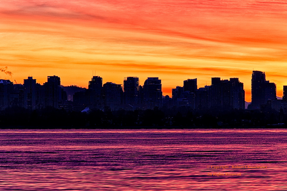 City Silhouette at Sunrise: A city landscape is silhouetted against a purple ocean and a fiery orange sunrise, Vancouver British Columbia, Canada.