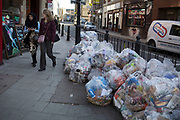 Veolia Environmental Services rubbish bags piled up on a street corner in Whitechapel in London, United Kingdom. This waste is set for recycling.