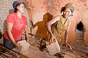 30 JUNE 2006 - PHNOM PENH, CAMBODIA: Workers stack bricks in a wood fueled kiln to bake them at a brick factory in Phnom Penh, Cambodia. According the United Nations Food and Agricultural Organization, there are more than 70 brick factories in Phnom Penh and its environs. Environmentalists are concerned that the factories, most of which burn wood in their kilns, contribute to deforestation in Cambodia. They are encouraging factory owners to switch to burning rice husks, as brick kilns in neighboring Vietnam do. The brick factories are kept busy feeding Phnom Penh's nearly insatiable appetite for building materials as the city is in the midst of a building boom brought by on economic development and the need for new office complexes and tourist hotels.   Photo by Jack Kurtz / ZUMA Press