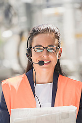 Portrait of a female engineer wearing headset with blueprint at geothermal power station, Bavaria, Germany