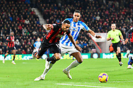 Callum Wilson (13) of AFC Bournemouth is challenged by Mathias Jorgensen (25) of Huddersfield Town but continues the attack during the Premier League match between Bournemouth and Huddersfield Town at the Vitality Stadium, Bournemouth, England on 4 December 2018.