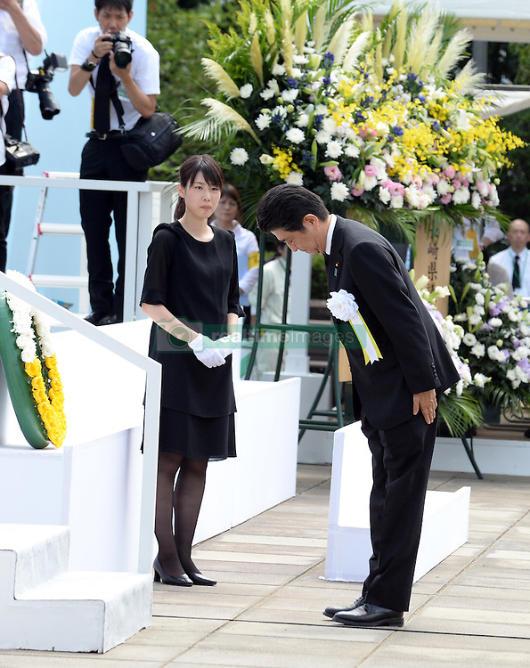 NAGASAKI, Aug. 9, 2016 (Xinhua) -- Japanese Prime Minister Shinzo Abe (R) bows during a ceremony commemorating the 71st anniversary of U.S. atomic bombing at the Peace Park in Nagasaki, on Aug. 9, 2016. To accelerate Japan's surrender in the World War II, the U.S. forces dropped two atomic bombs on Hiroshima and Nagasaki respectively on Aug. 6 and 9, 1945.  (Xinhua/Ma Ping) (syq) (Credit Image: © Ma Ping/Xinhua via ZUMA Wire)