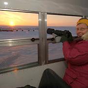 JoAnn Ziegler takes photos of the setting sun at Cape Churchill, near Churchill, Manitoba, Canada.