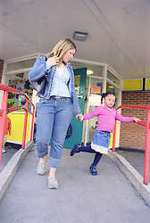 Single mother collecting young daughter from primary school,