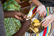 VSO ICS volunteers Romana Colman and Rebecca Hastie sit on the front step with Bibi preparing the evening meal. Volunteers stay with local families get the full experience. Lindi, Lindi region. Tanzania.
