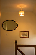 House room interior with miurror and picture at the top of stairs under ceiling light