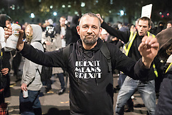 """© Licensed to London News Pictures . 05/11/2016 . London , UK . A man wearing a """" Brexit means Brexit """" t-shirt outside Downing Street . Supporters of Anonymous , many wearing Guy Fawkes masks , attend the Million Mask March bonfire night demonstration , in central London . Photo credit : Joel Goodman/LNP"""
