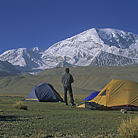 A trekker admires 24,750-foot Mustagh Ata from a camp in the Pamir Mountains of Xinjian, China.