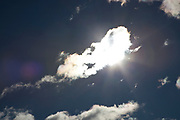 Sun in the sky behind cloud cover.