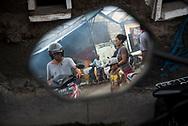 Bali, Indonesia - March 17, 2017: Indonesians, including a man on a motorbike on a street at the Jimbaran Fish Market in Jimbaran, Bali, Indonesia.
