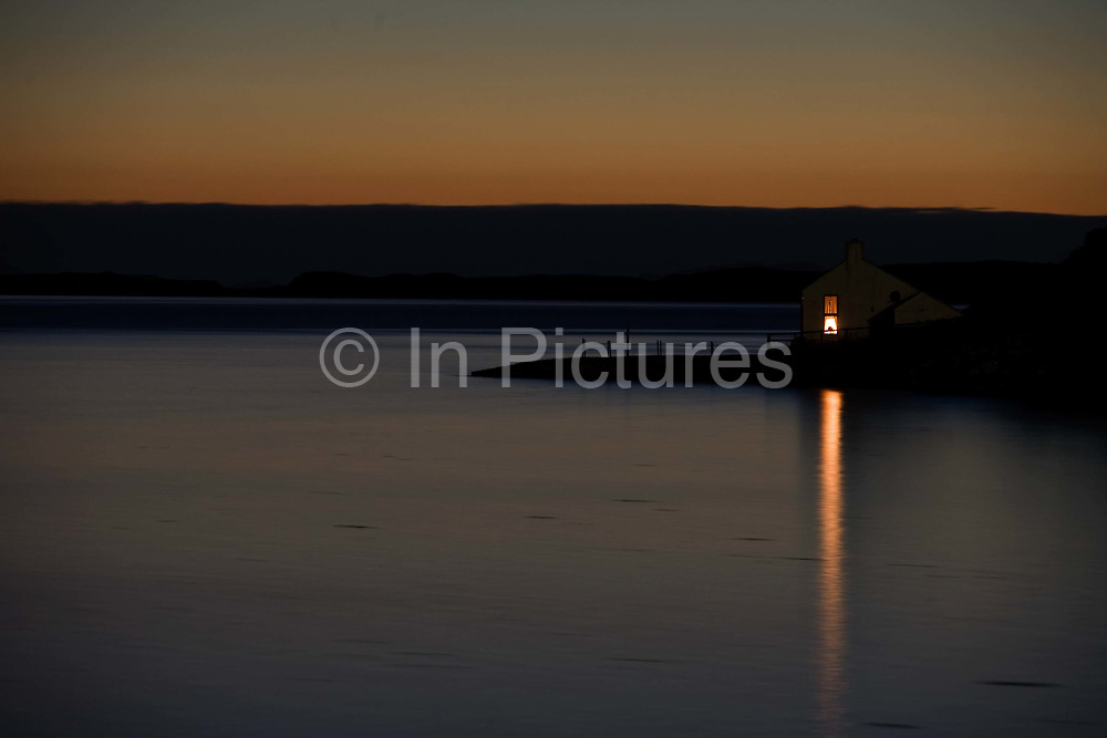The last light of day fades on the still waters of Sgeir Nam Biast, a bay overlooking Waternish Headland, near Dunvegan, north-west Isle of Skye, Scottish Highlands. A solitary light bulb glows from an upstairs room in this isolated cottage across the calm lake. The weather is perfect but unusual for one of the wildest parts of Britain. Farming practices have changed irreversably in a generation and many residents have English accents rather than that of native Scots islanders as city dwellers from the far south seek an alternative to urban lifestyles. The weather can have adverse effects on those unprepared for such wild conditions, especially during harsh winters when violent storms batter these Atlantic coasts. But old crofts have been converted to bed and breakfast homes, catering for tourist visitors who adore this form of idyllic escapism.<br /> <br /> .