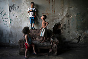 """In this Sept. 11, 2017 photo, children play inside a squatter building that used to house the Brazilian Institute of Geography and Statistics (IBGE) in the Mangueira slum of Rio de Janeiro, Brazil. Budgetary pressures and the conservative policies of President Michel Temer are translating into cuts in social services, including the """"Bolsa Familia"""" program that gives monthly small subsidies to qualifying low-income people. (AP Photo/Felipe Dana)"""