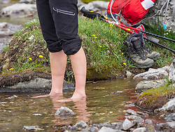 Woman hiker standing in water at riverbank, Gavarnie, France